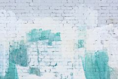 Una pared de ladrillo pintó el extracto con blanco y pintura de la turquesa Fondo, textura imagenes de archivo