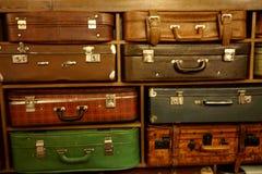 Una pared de las maletas que mienten en un estante imagen de archivo