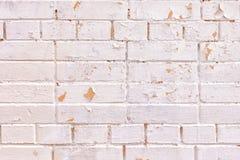 Una pared de los ladrillos de diversos tamaños La superficie es pintura rosácea ligera pintada Irregularidades, aspereza y peladu imágenes de archivo libres de regalías
