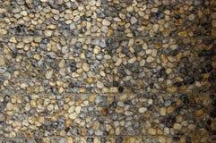 Una pared de piedra del guijarro hecha de piedras naturales con una mitad de ella en sombra Fotografía de archivo libre de regalías
