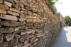 Una pared de piedra vieja grande en Bourton-en--agua en el verano Foto de archivo