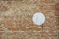 Una pared del ladrillo rojo-anaranjado viejo con pintó un círculo blanco grande Imagen de archivo libre de regalías