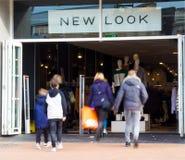 Una pareja adulta y dos niños que caminan en New Look hacen compras Imagen de archivo