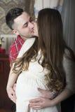 Una pareja beso-feliz apacible que aguarda el nacimiento de su niño Imágenes de archivo libres de regalías