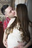 Una pareja beso-feliz apacible que aguarda el nacimiento de su niño Fotografía de archivo libre de regalías