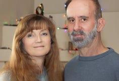 Una pareja casada con las luces de la Navidad detrás Fotografía de archivo