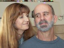 Una pareja casada con las luces de la Navidad detrás Foto de archivo