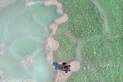 Una pareja casada que mira para arriba Viaje, viaje de la luna de miel al mar muerto Textura de los depósitos naturales de la sal foto de archivo