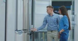 Una pareja de matrimonios joven abrir la puerta del nuevo refrigerador para examinar el diseño y la calidad antes de comprar en  almacen de video