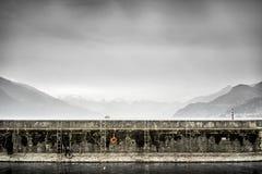 Una parete del porto sul lago Como con un traghetto e una neve ha ricoperto le colline nei precedenti Fotografia Stock