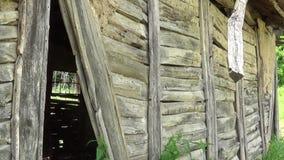 Una parete di legno con un foro in una vecchia casa abbandonata stock footage