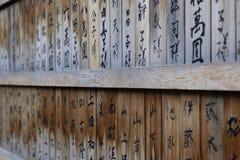 Una parete di legno del santuario nel Giappone con lo scritto di kanji Fotografia Stock Libera da Diritti