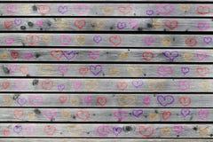 Una parete di legno grigia con molti cuori colorati immagini stock
