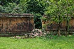 Una parete di pietra di una rovina antica con una grande lacuna della rottura da un angkor da parte a parte - Fotografia Stock