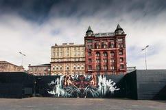 Una parete a Glasgow con arte dei graffiti della via Immagine Stock