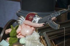Una parodia dell'Unione Sovietica L'angelo nudo di plastica in una maschera antigas ed il casco di un soldato sovietico con un Ka Fotografia Stock