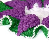 Una parte del tapetito hecho a ganchillo aislado en forma de los wi violetas de una uva imagenes de archivo