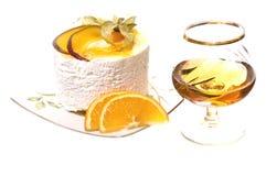 Una parte della torta e del vetro del cognac. fotografia stock