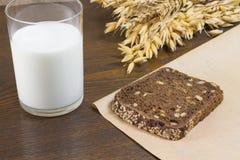 Una parte di pane nero, un vetro di latte Fotografia Stock