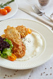 Una parte di pesce fritto con il purè del cavolfiore Immagini Stock