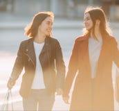 Una passeggiata di due donne insieme ai sacchetti della spesa di carta fotografie stock libere da diritti