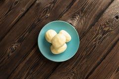 Una patata cruda fresca su un piatto su un fondo scuro del bordo di legno fotografie stock