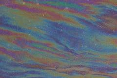 Una película iridiscente de la gasolina en la superficie de una carretera de asfalto Fotografía de archivo