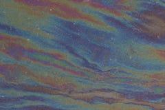 Una película iridiscente de la gasolina en la superficie de una carretera de asfalto Fotos de archivo