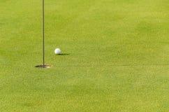 Una pelota de golf cerca al agujero Imagen de archivo libre de regalías