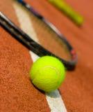 Una pelota de tenis con las raquetas en el fondo Fotografía de archivo