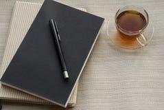 Una penna di vetro del taccuino e del tè immagini stock libere da diritti