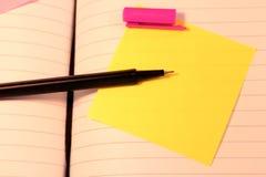 Una penna ritenuta rosa con il cappuccio fuori dalle bugie sopra una nota appiccicosa gialla in un libro aperto del diario fotografia stock libera da diritti