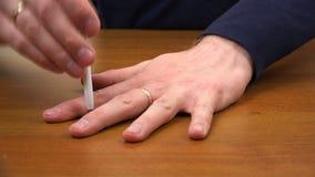 Una penna a sfera perfora lo spazio fra le dita della mano sinistra archivi video