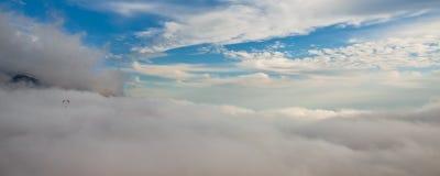 Una pequeña ala flexible vuela sobre el mar de las nubes blancas, un panoram imagen de archivo