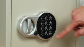 Una pequeña caja fuerte con una cerradura electrónica del código La mano del ` s del hombre abre la caja fuerte y toma los dólare metrajes