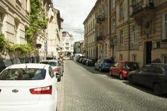 Una pequeña calle alineada con los coches fotos de archivo libres de regalías