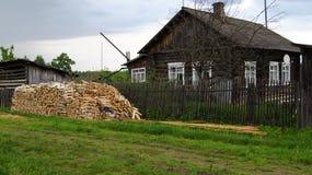 Una pequeña casa con madera del fuego en la aldea rusa. Fotografía de archivo