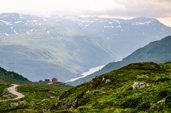 Una pequeña casa roja en el horizonte sobre el fiordo profundo y estrecho en Noruega, Europa Foto de archivo libre de regalías