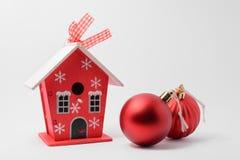 Una pequeña casa y bolas del árbol de navidad Foto de archivo libre de regalías