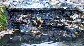 Una pequeña cascada está en un parque Foto de archivo
