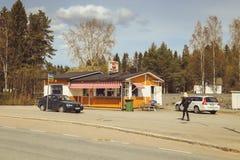Una pequeña ciudad en Finlandia, un café del borde de la carretera, coches en el camino y tiendas Día de verano de la ciudad finl foto de archivo