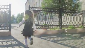 Una pequeña colegiala divertida en uniforme escolar y una cartera en sus hombros corre a la escuela metrajes