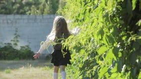 Una pequeña colegiala divertida en uniforme escolar y una cartera en sus hombros corre a la escuela almacen de metraje de vídeo