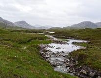 Una pequeña corriente a través de las montañas escocesas Imágenes de archivo libres de regalías