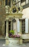 Una pequeña fuente de piedra que sostiene las flores rosadas con los ángeles tallados que se colocan en el top Fotos de archivo