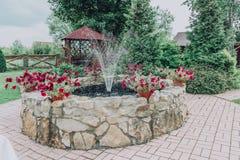 Una pequeña fuente en el jardín de la piedra con las flores de la petunia fotos de archivo libres de regalías