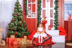 Una pequeña hija abre un regalo de la sorpresa Año Nuevo del concepto, feliz Imagen de archivo libre de regalías