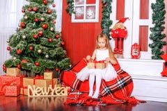 Una pequeña hija abre un regalo de la sorpresa Año Nuevo del concepto, feliz Fotografía de archivo libre de regalías