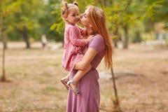 Una pequeña hija camina con la mamá en el parque fotografía de archivo