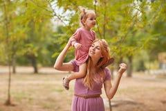 Una pequeña hija camina con la mamá en el parque imágenes de archivo libres de regalías